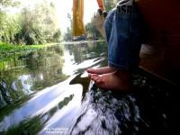 С лодки ногами в воде
